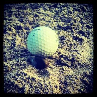golf bola bunker apoyada piedra